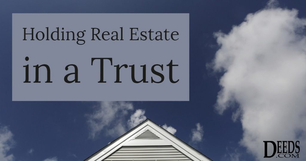Image of the peak of a house with a blue sky background and fluffy clouds. Captioned: Holding Real Estate in a Trust.