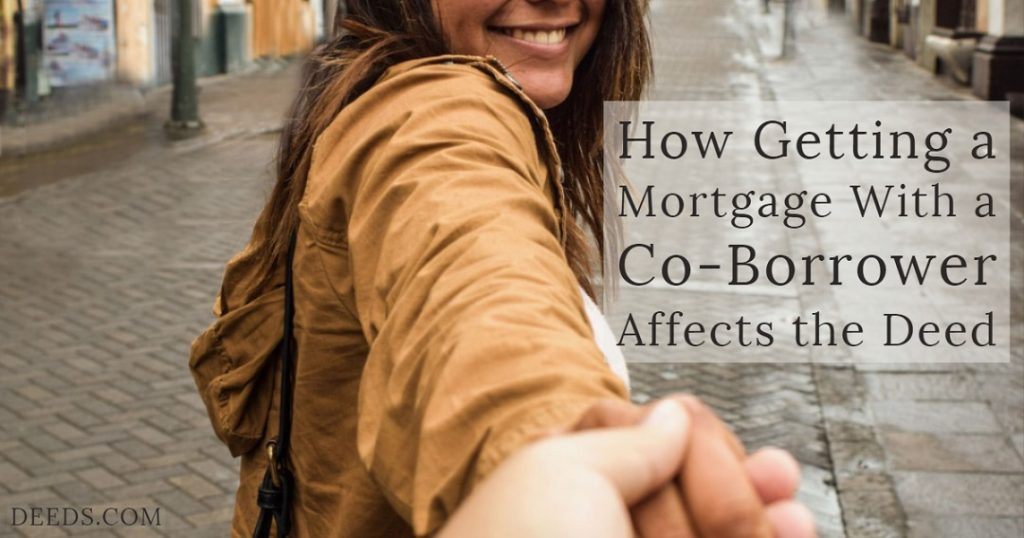 Image of a smiling woman on a house lined street holding the hand of a person while leading them down the street. Captioned: How Getting a Mortgage with a Co-Borrower Affects the Deed