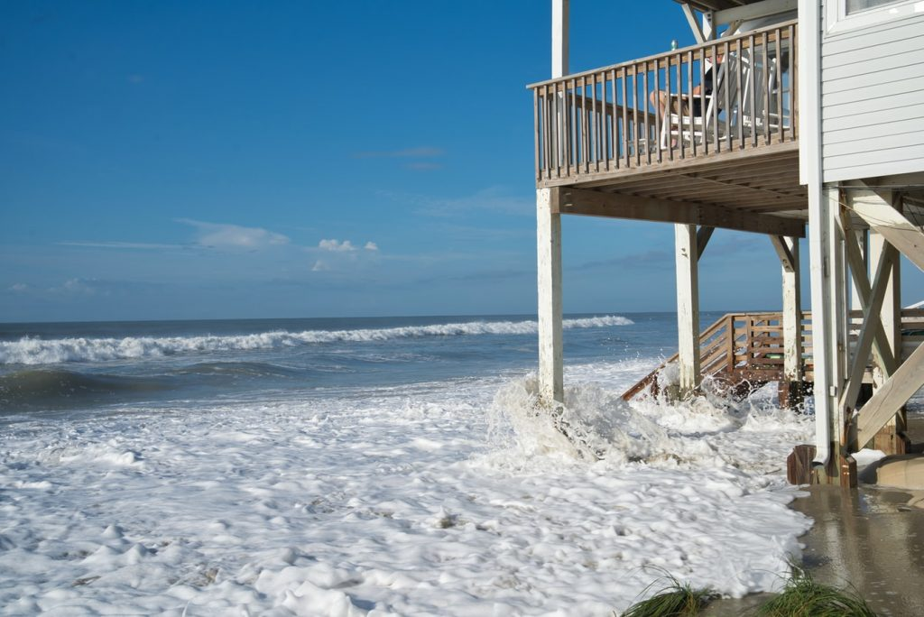 Image of a house with ocean waves splashing under it meant to represent rising sea levels caused by climate changing. Photo by Clint Patterson via Unsplash