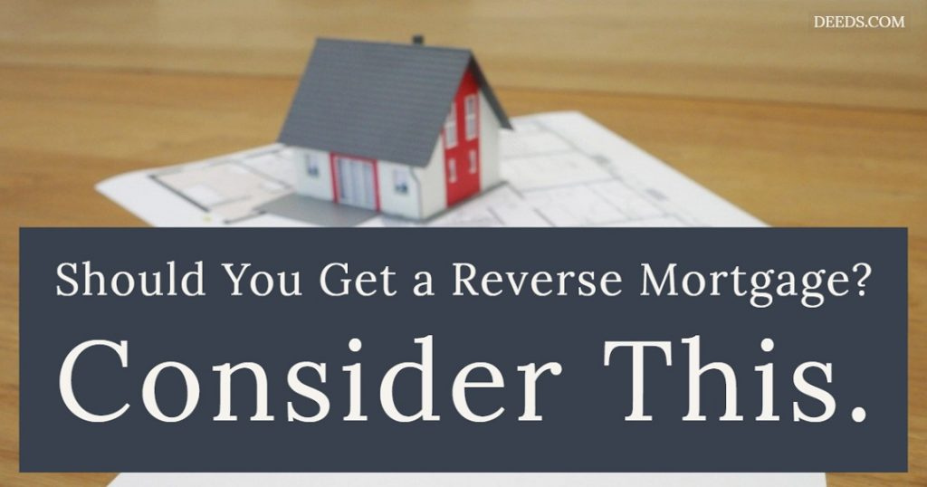 Image of a small paper model of a house sitting on blueprints on a table. Captioned: Should You Get a Reverse Mortgage? Consider This.