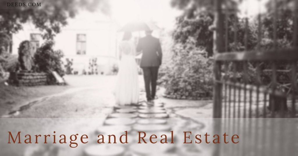 Image of a couple under an umbrella walking down a path towards a house appearing to be in a wedding, getting married. Captioned: Marriage and Real Estate