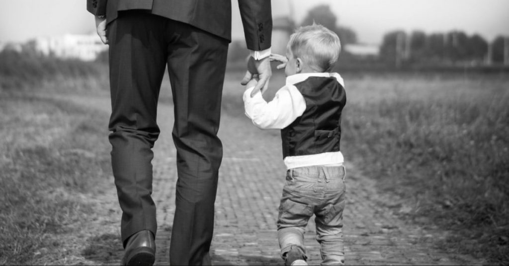 Image of a father and son holding hands walking along a brick paved path toward a house in the distance.