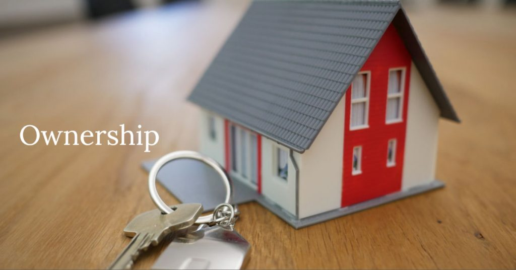 Image of a small model or toy house sitting on the floor next to a key chain with a house key on it. Titled: Ownership