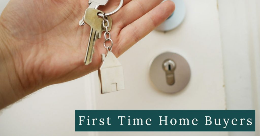 Image of a person's hand holding a set of house keys on a key chain in front of a door to a house. Captioned: First Time Home Buyers