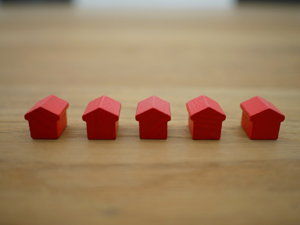 Image of five small blocks of wood shaped into houses and painted red setting on a table.