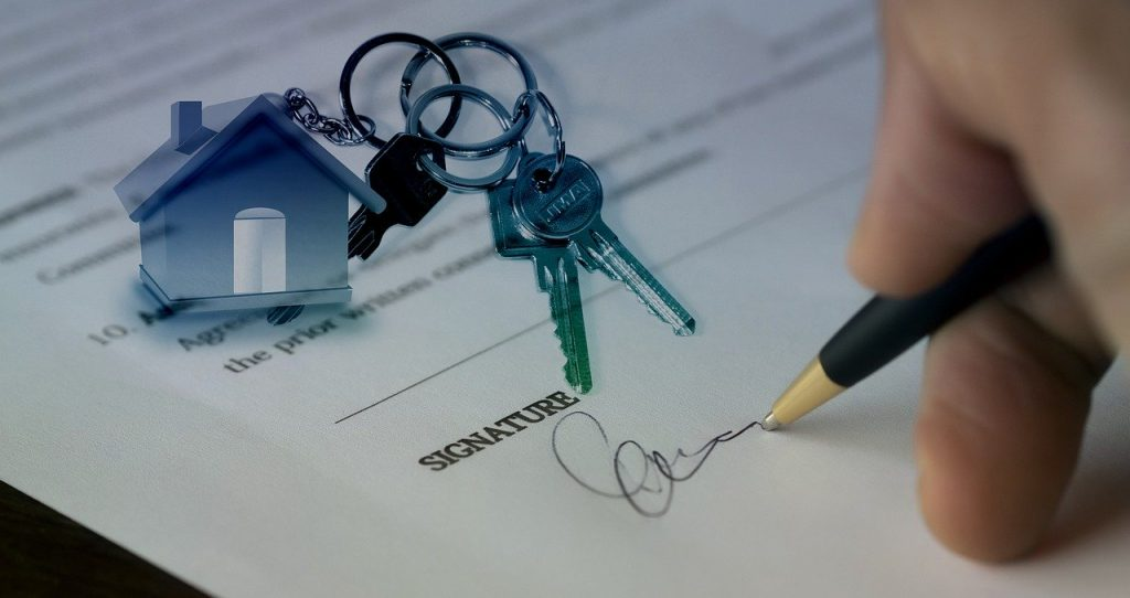 Image of a hand holding a pen signing a legal document.