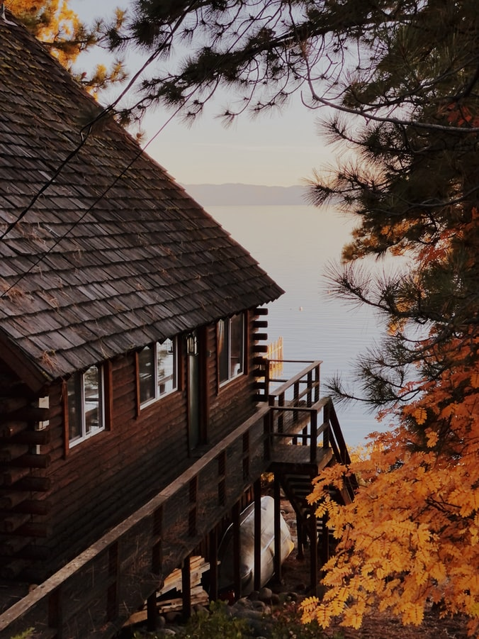 Image of a cabin style house surrounded by large trees with a lake and mountains in the background.