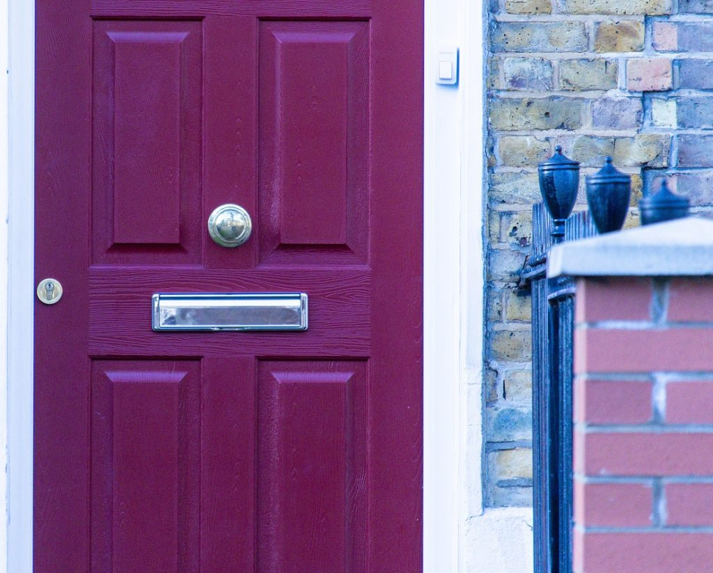 Close up image of a dark red door on a house. Captioned: Bargain and Sale Deed vs. Quitclaim Deed