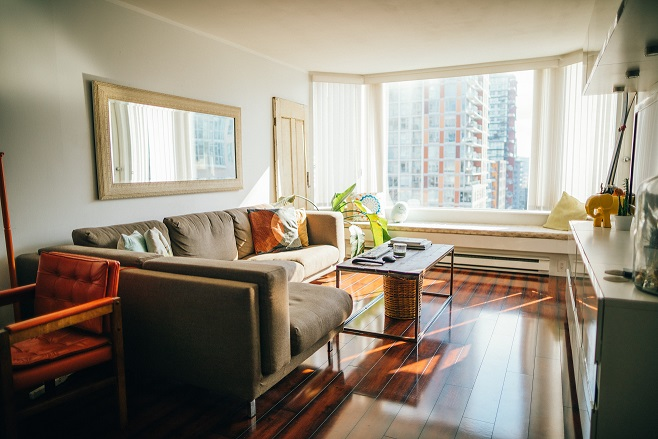 Image of the inside of a condo living room with typical furniture and a window looking out at another condo building.