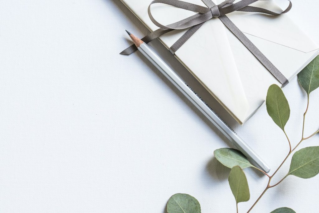 Image of gift envelopes with a ribbon and a pencil. Article about real estate gift deeds specific to Arizona and Florida.