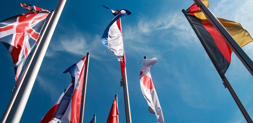 Image looking up at several international flags on flag poles with a blue sky in the background. Captioned: Immigration Status and Real Estate