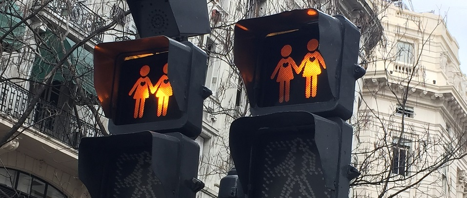 Image of crosswalk signals fashioned to have same sex couples indicating when to cross the street. Captioned: LGBT+ and Real Estate Ownership