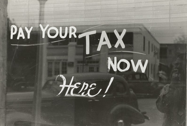 "Historical image of a window on a downtown building with the words ""Pay Your TAX Now Here!"" painted on it. Captioned: Back Taxes Can Impact Your Real Estate Title"