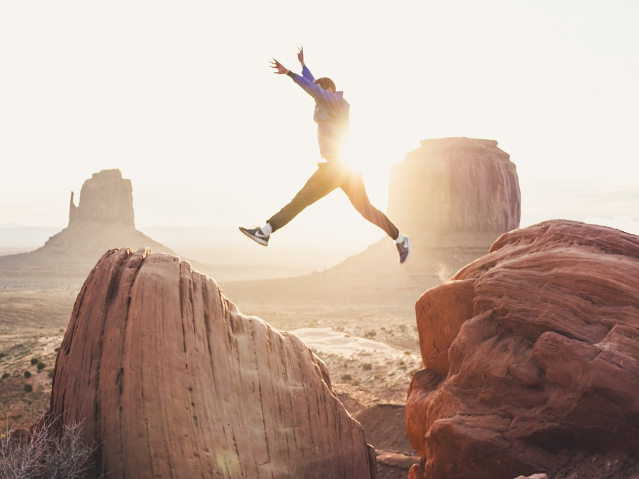 Image of a person leaping across large boulders with the sun shining brightly at their back. Captioned: Ready For Sole Homeownership?