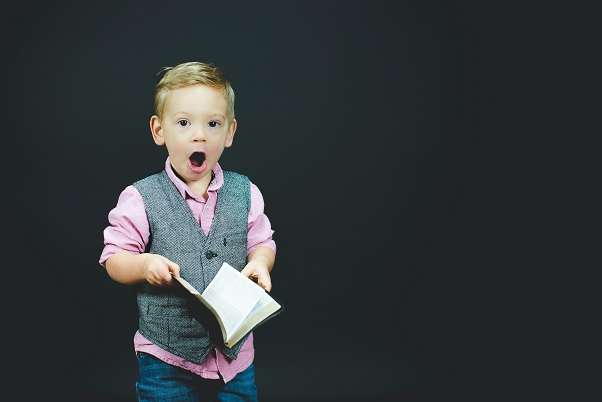 Image of a child holding a book with a very surprised like on their face.  Captioned: When you least expect it... What You Need To Know About Unrecorded Real Estate Liens