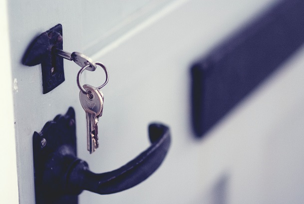 Image of a house door with keys in the lock. Captioned: How a Contract for Deed Works.