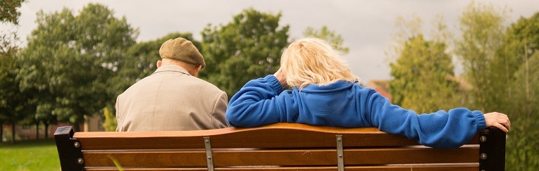 Image of an elder couple sitting on a park bench with their backs to us and a tree filled parked in the foreground. Captioned: Elders and Real Estate Fraud