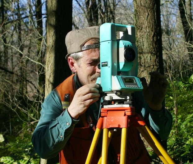 Image of a person in the woods using survey equipment to do a property survey.