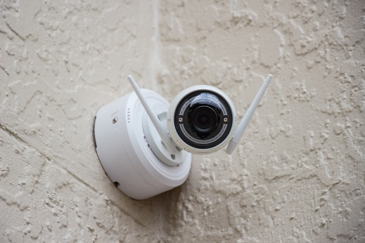 Image of a security camera on a wall. Captioned: Is Smart Home Technology Turning Property Managers Into Spies?