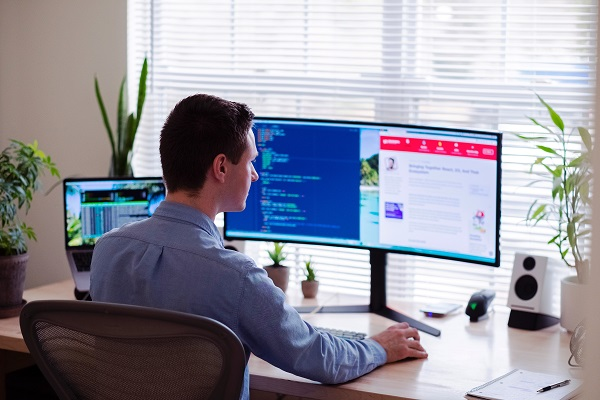 Person in a blue dress shirt sitting at a desk with several computer monitors. Captioned: Mortgage Tech: no Longer an Oxymoron.