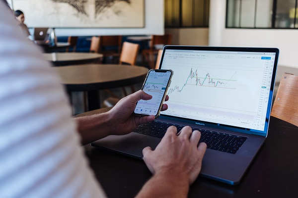 Image of a person using a smart phone and a laptop computer at the same time to keep track of stock information. Captioned: Real Estate Stocks and IPOs: Should You Invest?