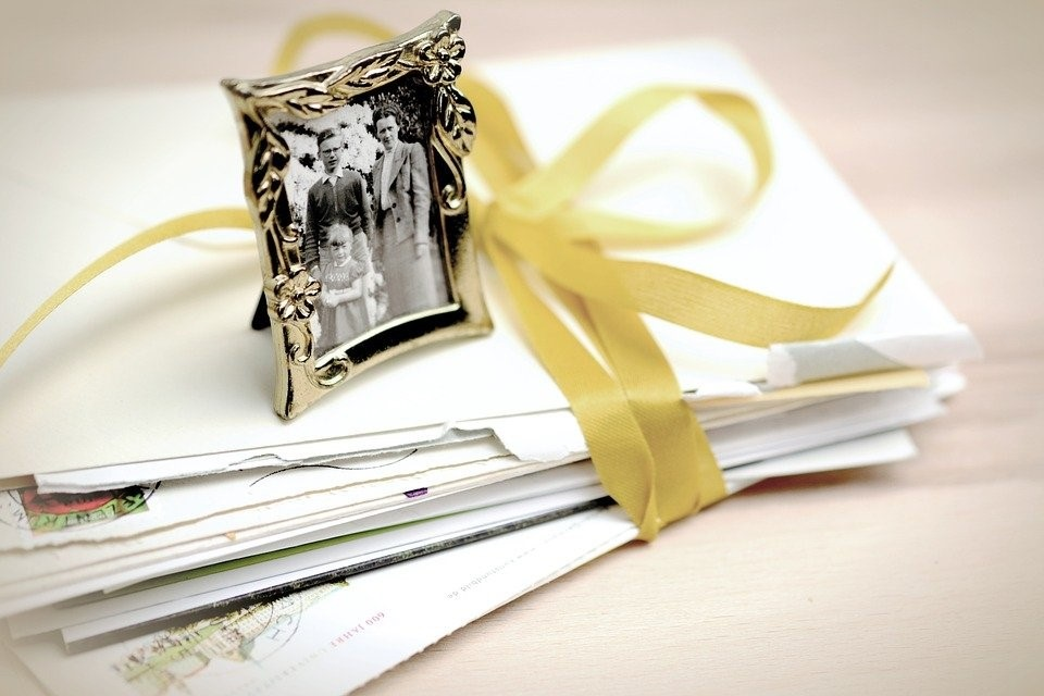 Image of a stack of opened letters bundled together with yellow ribbon and a tiny old picture in a frame on top. Captioned: Should You Transfer Your Home to Your Children Now, or Leave It in Your Will?