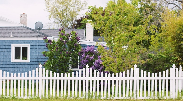 Image of the outside of a house, side view, with the traditional white picket fence. Captioned: DIY Renovations?