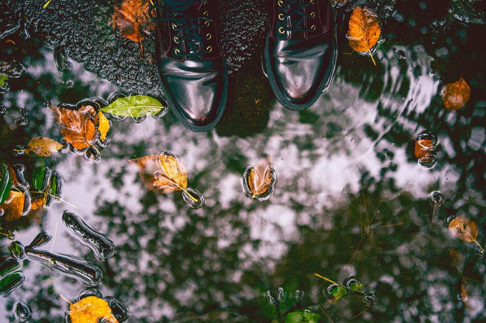 Image of someone's feet next to a puddle of water with leaves in it. Captioned: Inundated, The National Flood Insurance System