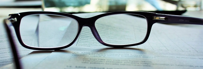 Image of reading glasses laying on paperwork. Captioned: An Opinion of Title: What Home Buyers Should Know
