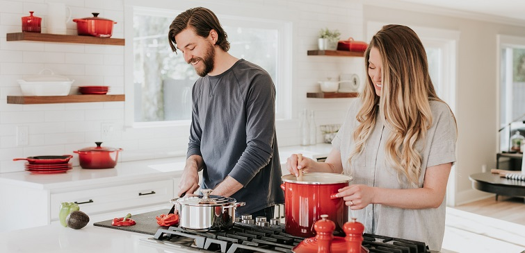 Image of a seemingly happy couple in a kitchen, cooking together. Clearly a fantasy piece that will make any couple married for longer than 48 hours throw up in their mouth a little bit... enjoy.