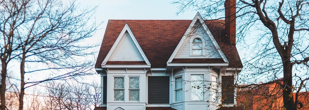 Image of the front of an older two story house. Captioned: Guide to Buying an Estate Sale Home