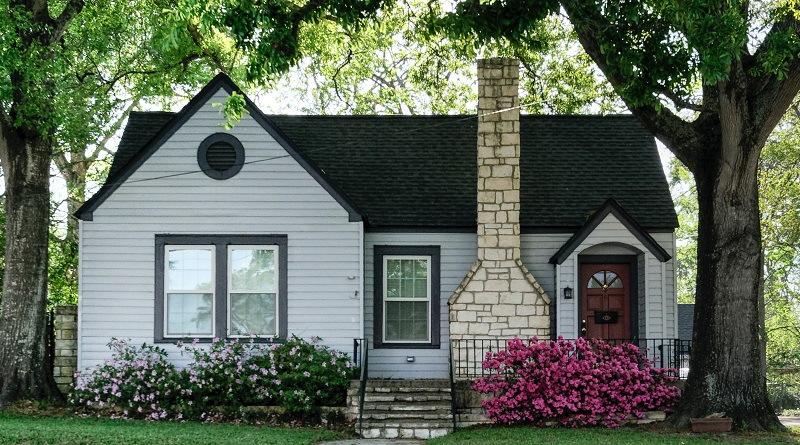 Image of a small, old house with a nice chimney. Captioned: Guide to Selling an Inherited Home