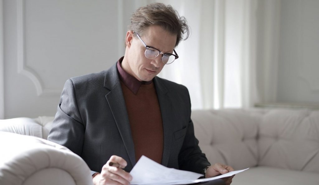 Image of a smartly dressed person reviewing a legal document, specifically a Grant Deed legal document.