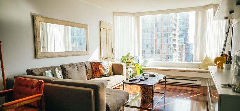 Picture of a small furnished living room with a big window looking outside. Captioned: A Guide to Private Mortgage Insurance