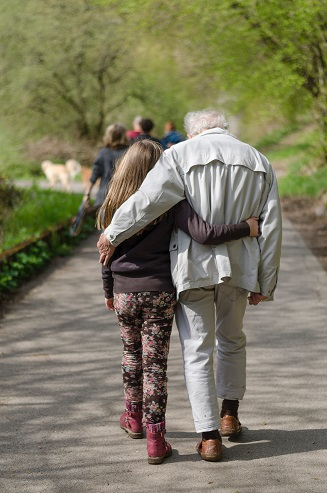 Image of a grandfather and grand daughter walking together along a path. Captioned: Selling the Life Estate Property
