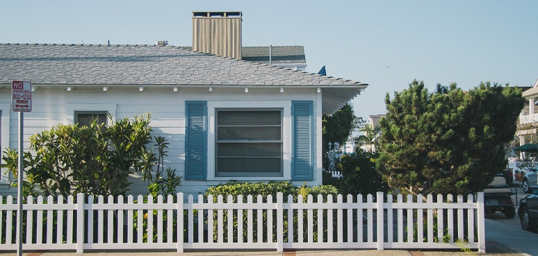 Image of the outside of a house in a city. It has a white picket fence and nice landscaping. Captioned: What Is a Short Sale — And What Does It Mean for Home Buyers?