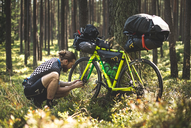 A person in the woods fixing a bicycle. Captioned: Strengthen Your Position to Finance Your Home