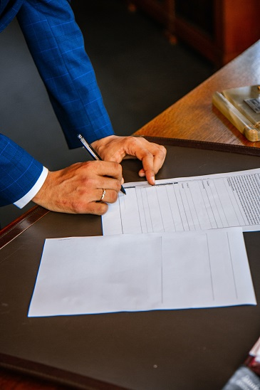 Image of a person signing documents and going of a checklist. Here is a checklist of QPRT questions to present to your CPA and your estate planning attorney