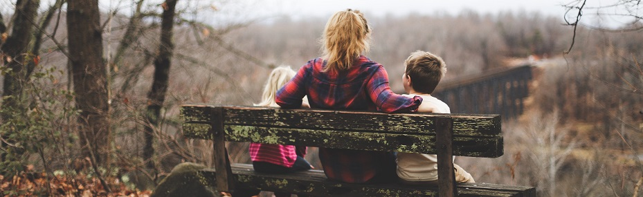 Image of a person sitting on a bench in a wooded area with two children. Captioned: Is It Time to Place Your Home in a Living Trust?