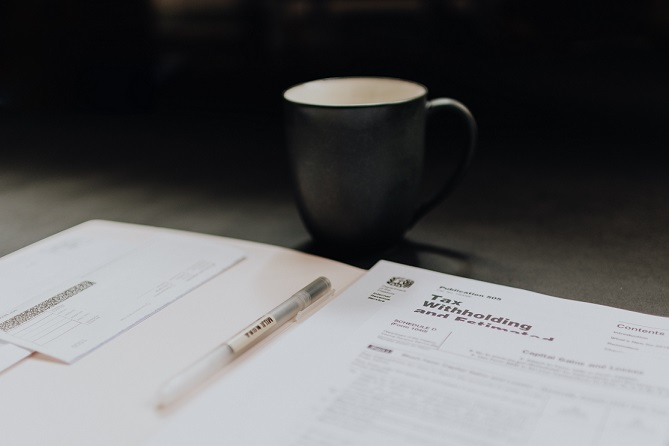 Image of a coffee cup and a pen sitting on tax forms. Captioned: Paying Taxes as the Owner of an LLC