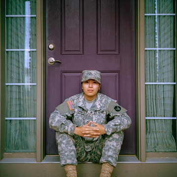Image of a soldier sitting on the front steps of a home. Welcome home veteran.