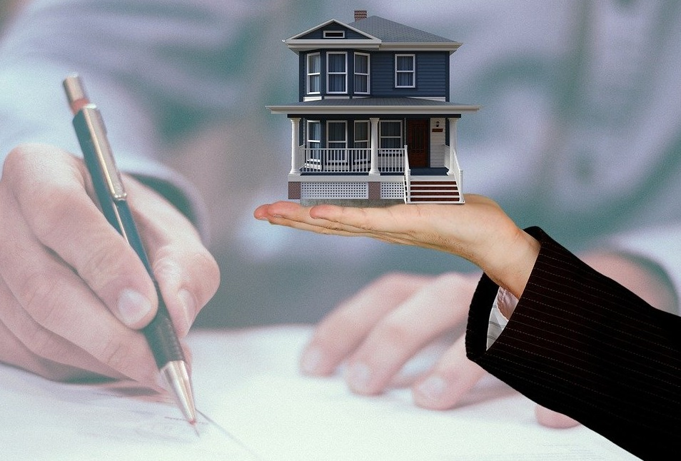 Image of a person signing documents related to buying a house while it appears that someone else is holding a house in their hand.