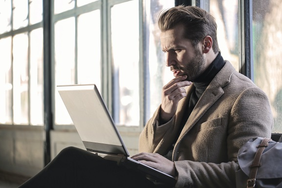 Image of a person in deep thought looking at a computer. Captioned: Interest Rates Are Low. Does That Make Refinancing a Good Deal?
