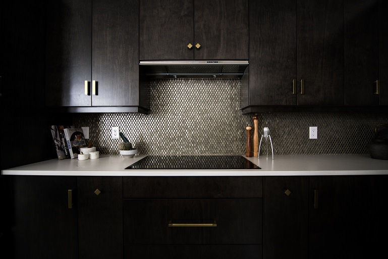 Image of a residential kitchen area, sink, counter, and cabinets. Dark lighting with no windows.