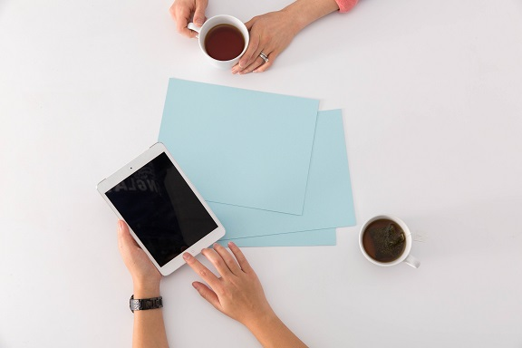 Image of some paper, a couple of cups of coffee, and hands using a tablet computer. Captioned: Hot Tips for Tax Season — And for Hopeful Homeowners