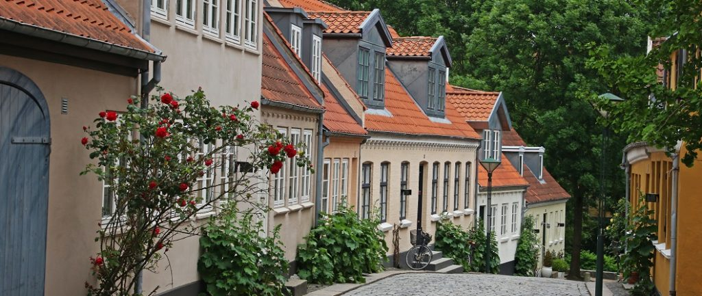 Closely built row of houses on a cobblestone street. Captioned: The Pros and Cons of Consolidating Your Home Loans