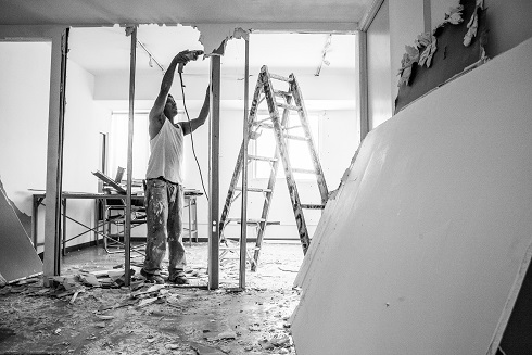 Image of a construction worker remodeling a house. Captioned: Conventional Rehab Loans