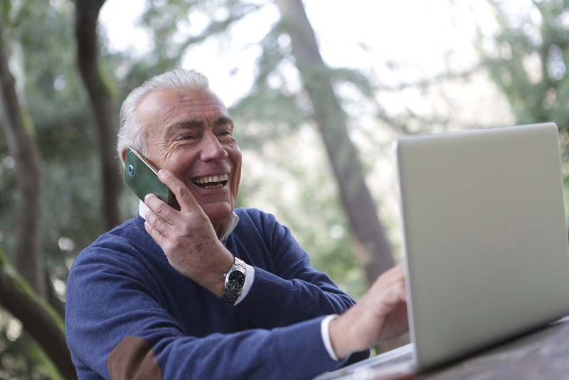 Image of a person sitting outside talking on a phone and using a computer at the same time. They seem very happy.
