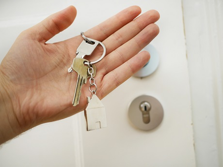 Picture of a person's hand holding a set of house keys in front of the front door to a house. Captioned: How Can the Seller Offset Profits and Reduce Taxable Gains?