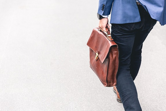 Image of a person with a leather briefcase walking away from the camera. Captioned: How Much Will You Pay Your Real Estate Agent?